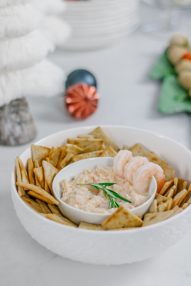 close up of seafood dip and crackers in white bowls