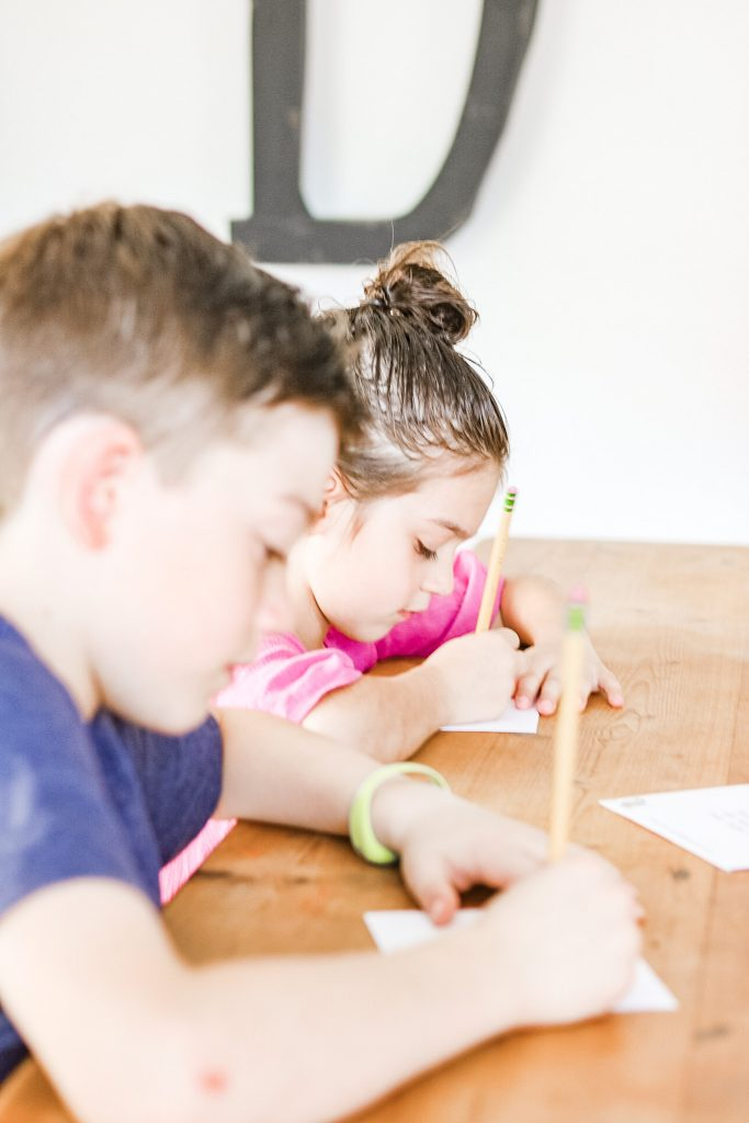 two children homeschooling at a wood dining table