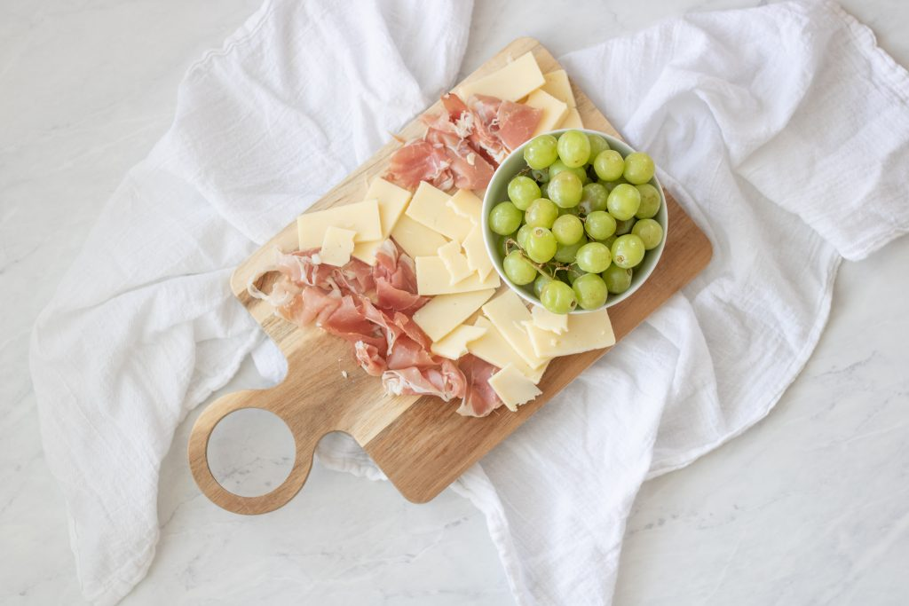 proscuitto, white cheddar and green grapes on wood cutting board