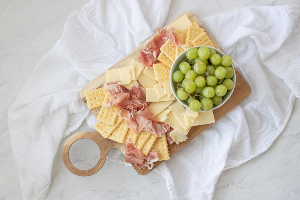 proscuitto, white cheddar, crackers and green grapes on wood cutting board