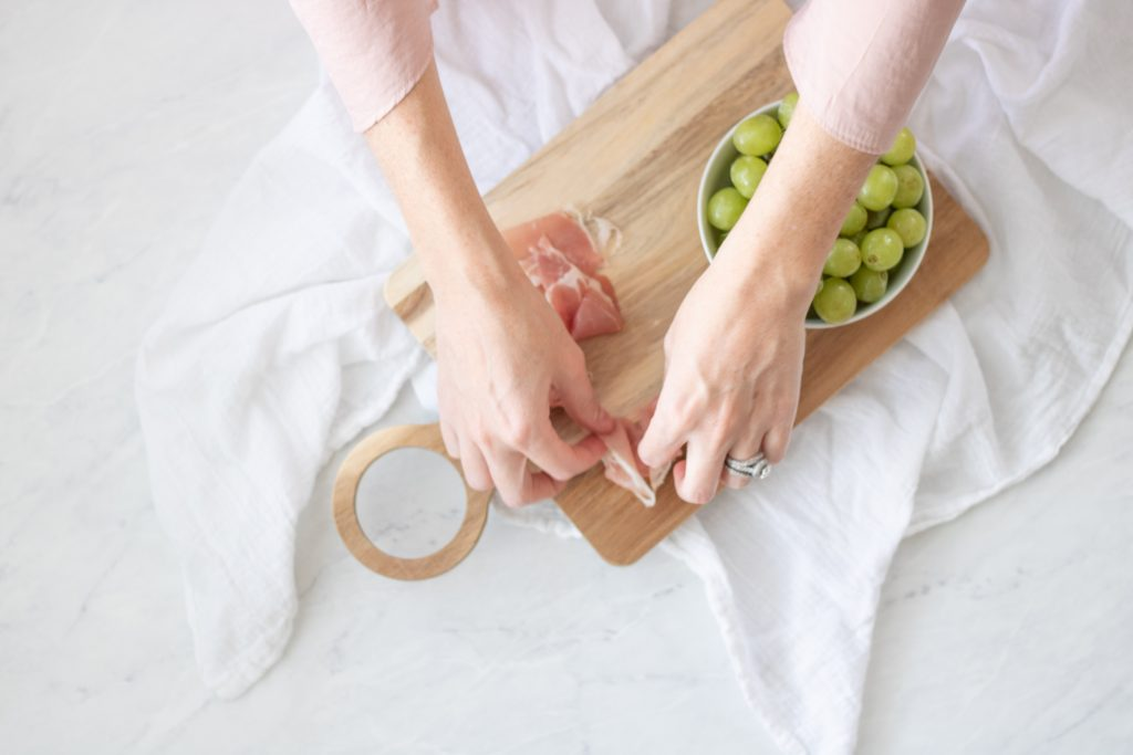 proscuitto and green grapes on wood cutting board