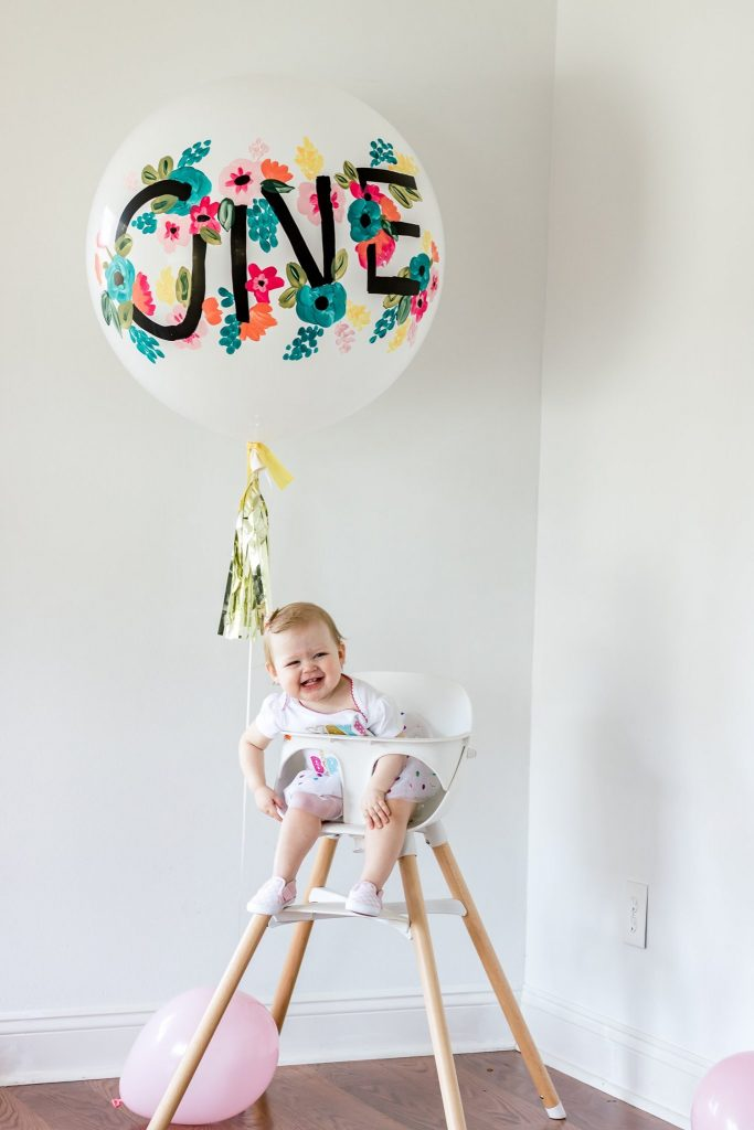 baby sitting in lalo chair with oversized birthday balloon