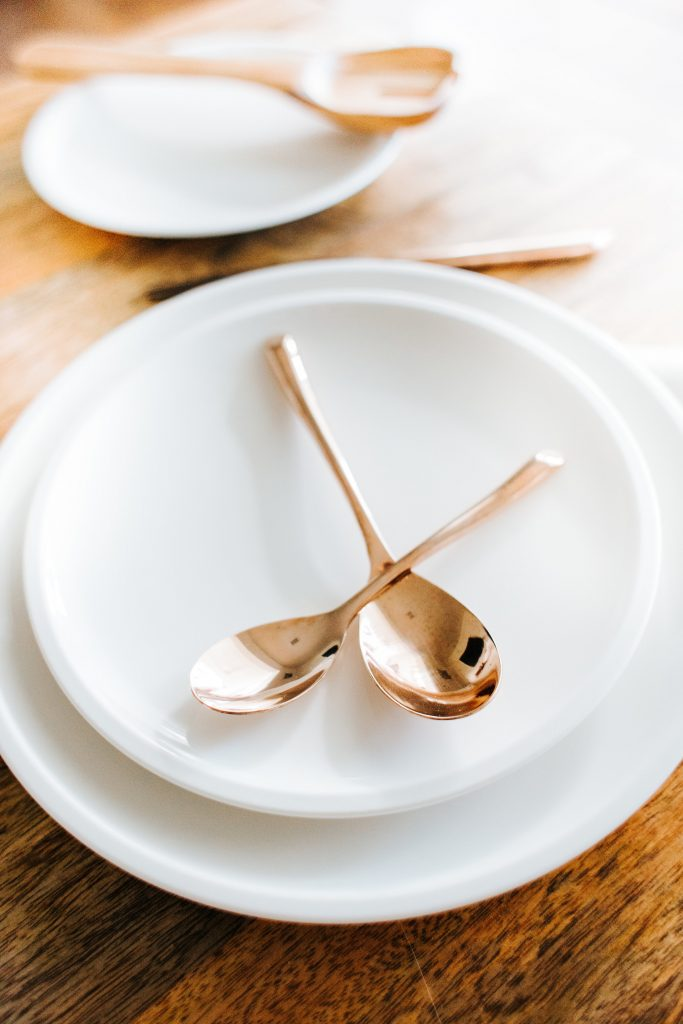 close up of white everyday dinnerware white salad plate stacked on white dinnerplate with copper spoons overlapping on top