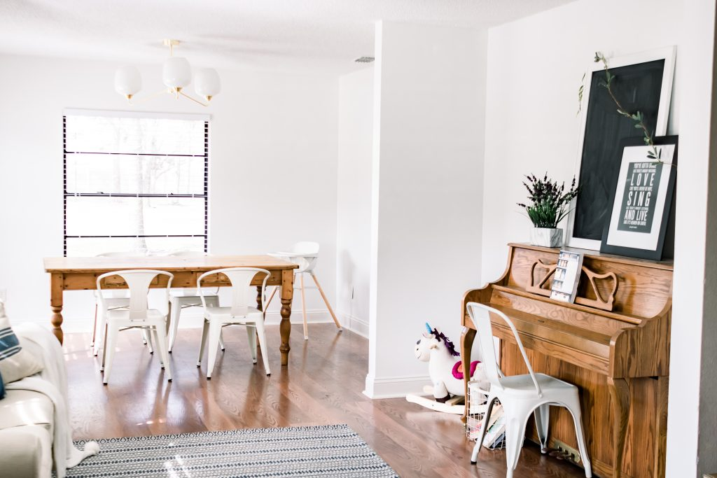 less is more, white dining and living room with wooden farm table and white metal chairs