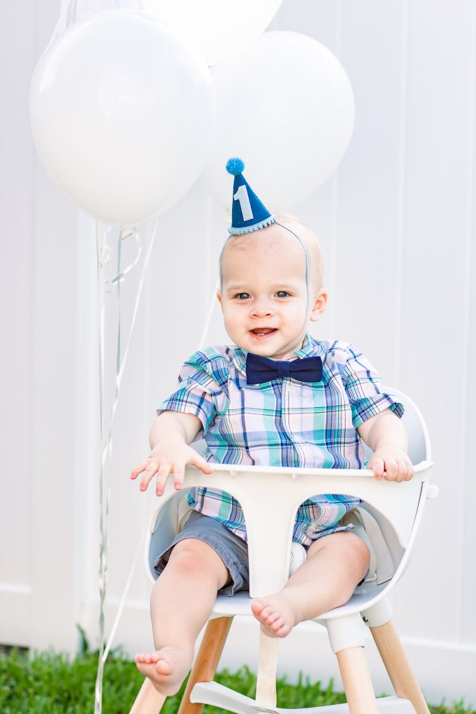 baby boy sitting in lalo chair in plaid shirt and birthday hat