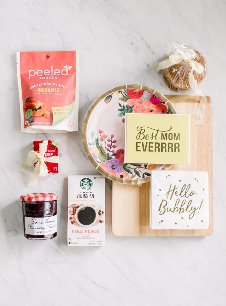 flat lay of cutting board raspberry preserves starbucks instant coffee yogurt covered raisins stroopwafels peeled snacks and decorative paper plates napkins and a mother's day card