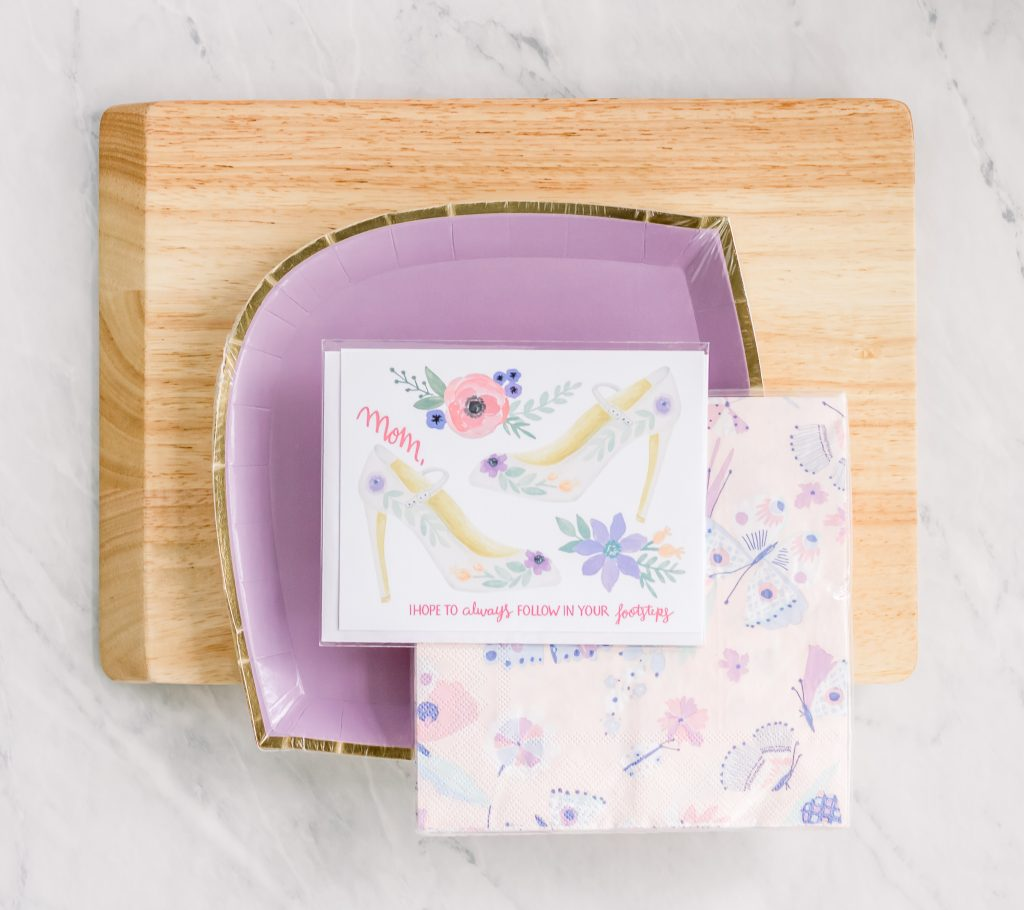 cutting board with purple decorative paper plates napkins and mother's day card stacked on top
