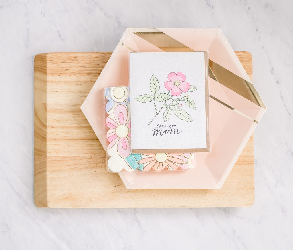 cutting board with pink decorative paper plates napkins and mother's day card stacked on top
