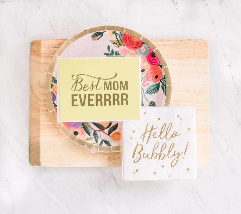 cutting board with floral decorative paper plates napkins and mother's day card stacked on top
