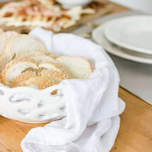 White ceramic bread basket lined with flour sack and filled with fresh loaf of bread