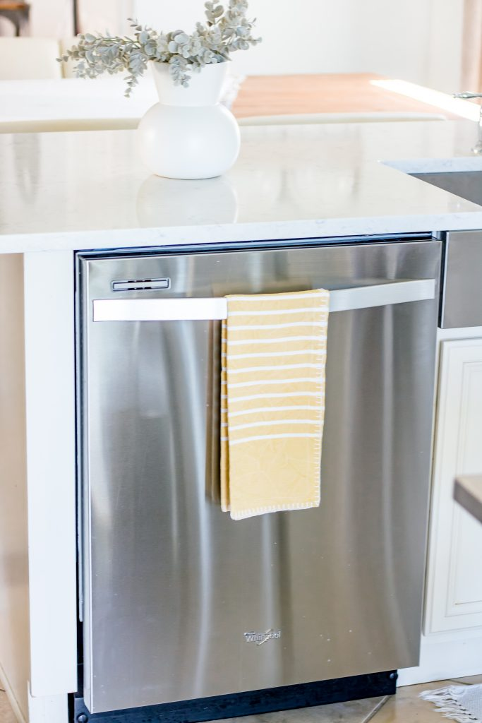 Yellow and white striped tea towel hanging on stainless steel dishwasher
