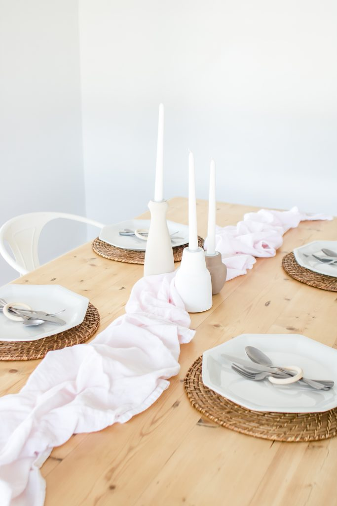 Natural pine wood dining room table set with wicker placemats, white dishes, flour sacks as a table runner and a set of decorative candle holders.