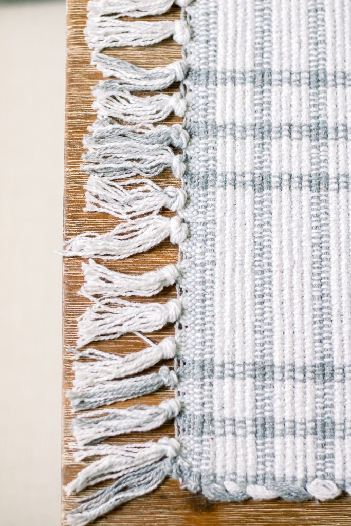 Close up of white and grey plaid table runner with tassel fringe