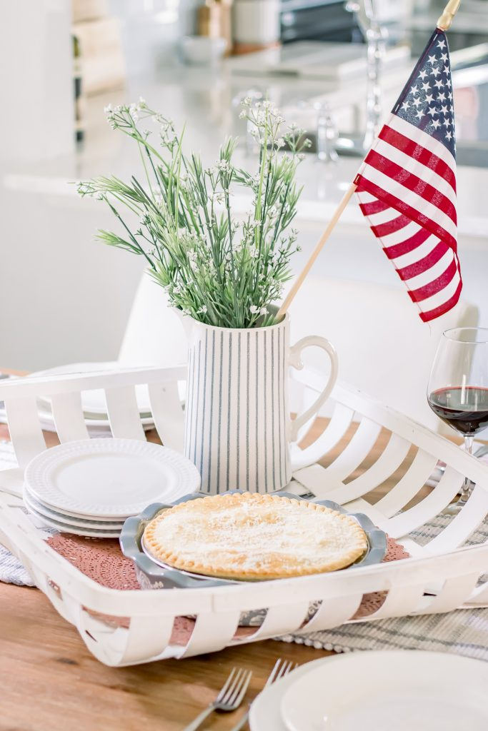 Summer table decor including a white tobacco basket filled with a white porcelain pitcher with faux greenery and an American flag, white salad plates and a frozen pot pie in a pale blue pie dish