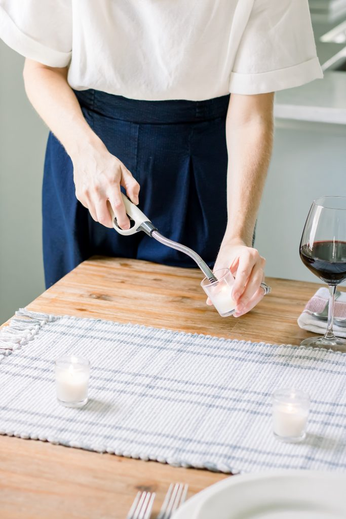 Close up female lighting a white votive candle for a tablescape