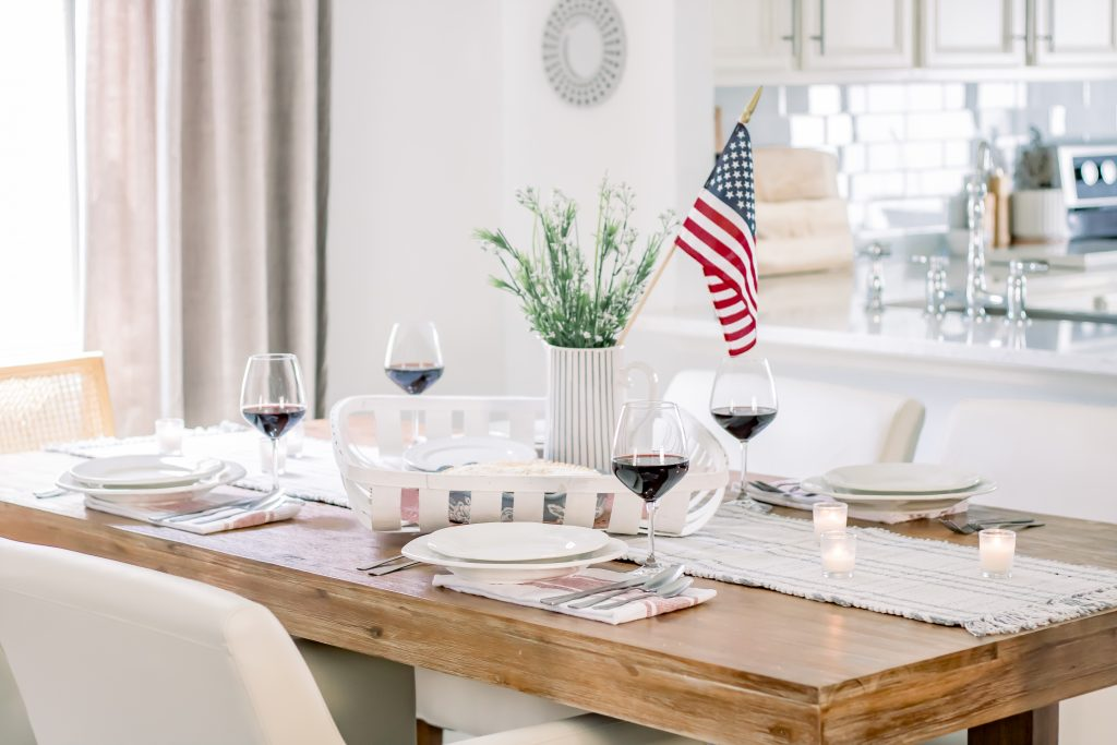 Wide shot of wood dining table set with red, white and blue summer table decor for a 4th of July tablescape