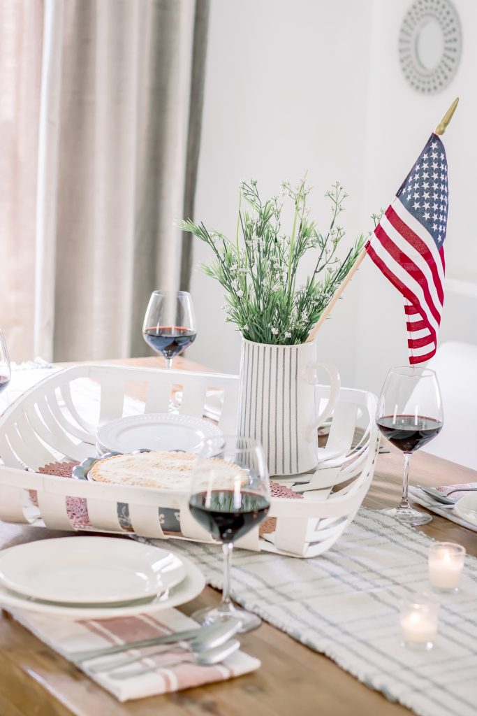 A wood dining table set with red, white and blue summer table decor for a summer dinner party