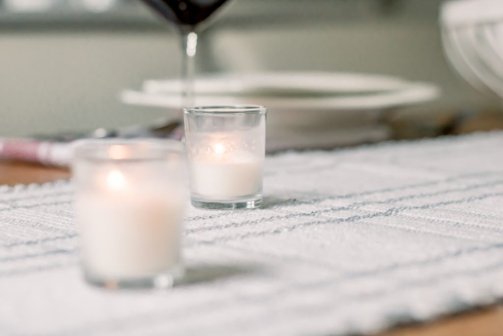 Close up of white votive candles on white and grey plaid table runner