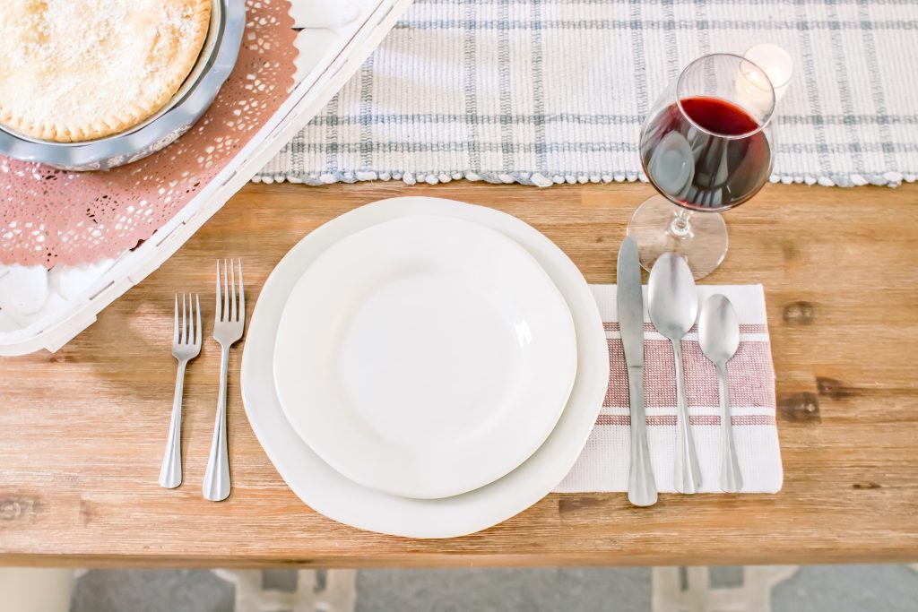 Simple red and white place setting with white dinner and salad plates, red and white striped dinner napkins, silverware and a red wine glass