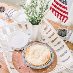 July 4th Centerpiece with white tobacco basket, pale blue pie plate, white dishes and white porcelain pitcher with greenery and American flag