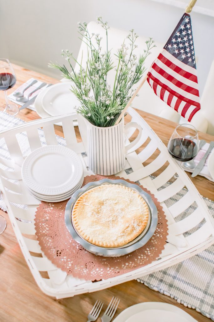 July 4th Centerpiece and summer table decor with white tobacco basket, pale blue pie plate, white dishes and white porcelain pitcher with greenery and American flag