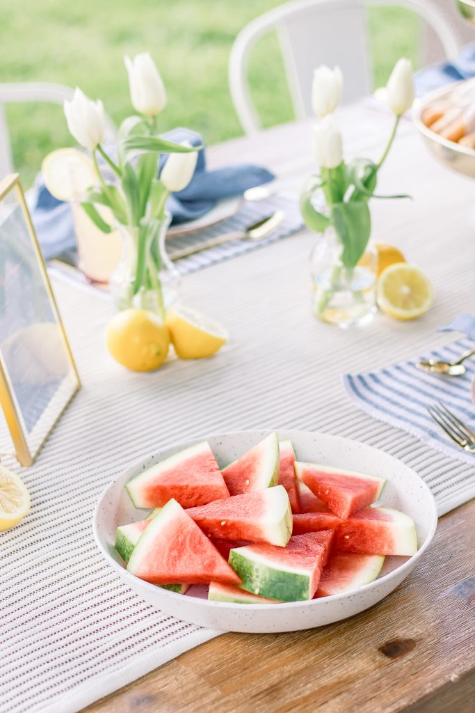 watermelon in a bowl on a wooden dining table outside