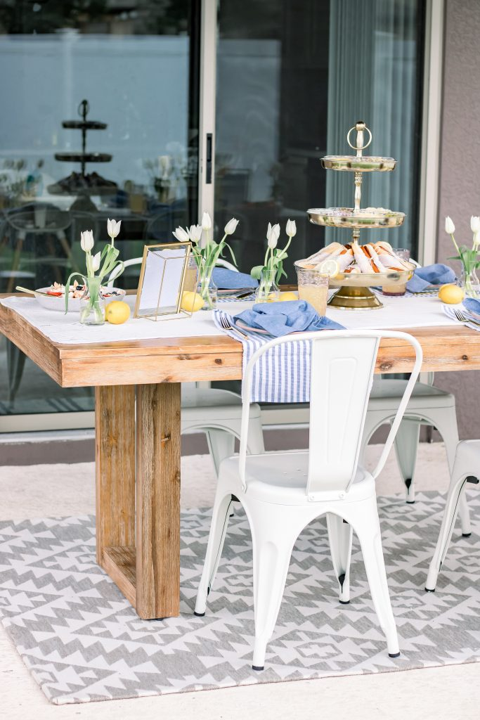 white metal chairs and a wood dining room table on outside patio for an Intimate Fourth of July Soiree