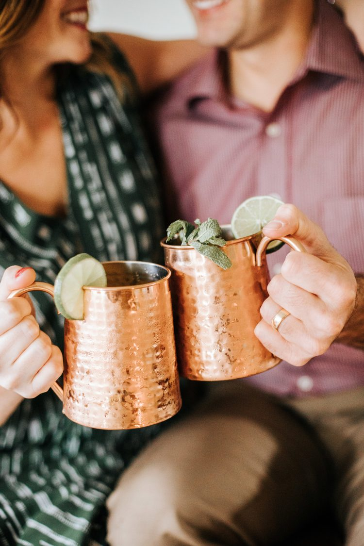male and female snuggled up holding copper mugs with limes and toasting