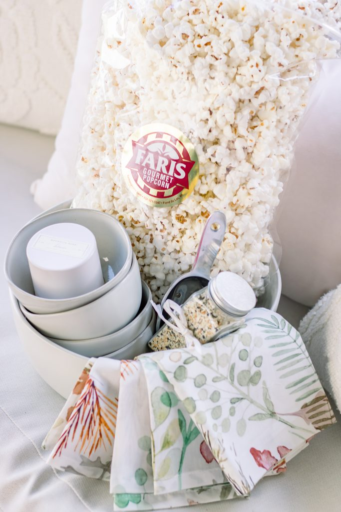 A unique Summer hostess gift comprised of cream stoneware bowl filled with mini cream stoneware bowls, white soy wax candle, floral linen napkins, everything bagel seasoning, metal ice scoop and a bag of white popcorn