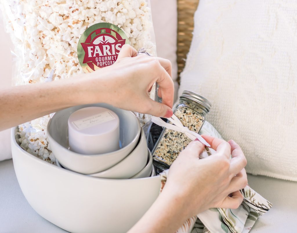 A woman tying a bow on a unique Summer hostess gift comprised of cream stoneware bowl filled with mini cream stoneware bowls, white soy wax candle, floral linen napkins, everything bagel seasoning, metal ice scoop and a bag of white popcorn