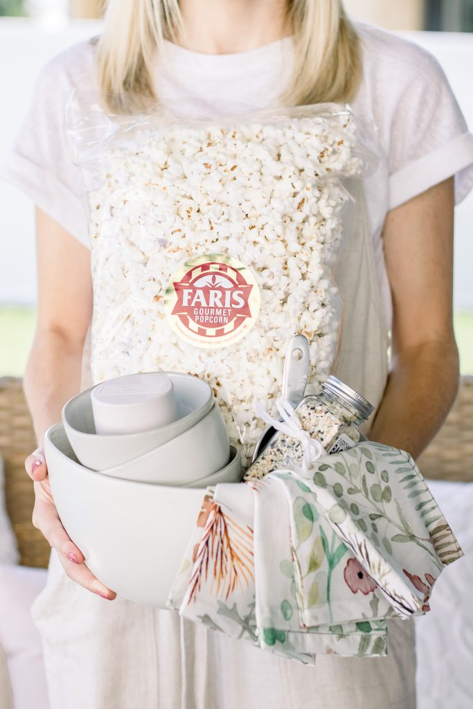 A woman holding a cream stoneware bowl filled with cream stoneware mini bowls, a set of floral linen napkins, everything bagel seasoning, metal ice scoop and bag of white popcorn as a unique Summer hostess gift