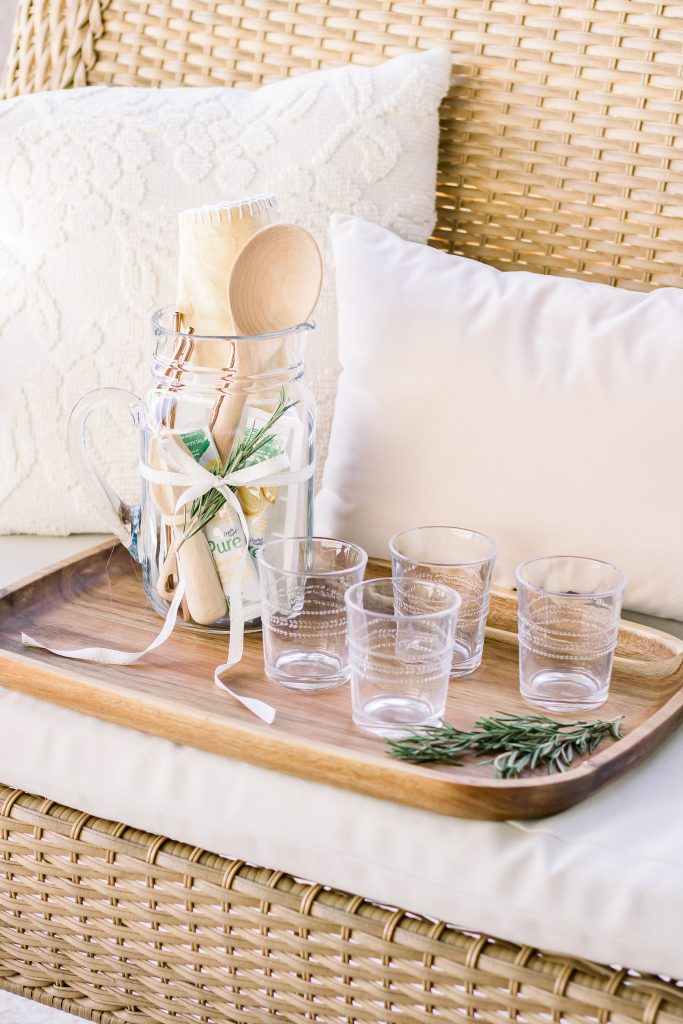 A unique Summer hostess gift comprised of a clear pitcher, lemonade packets, wooden mixing spoon, lemon juicer, white silicone ice cube tray, yellow tea towel and emboseed clear tumblers