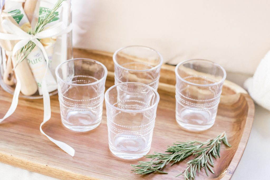 Clear glass tumblers on an acacia serving tray being used as a unique Summer hostess gift