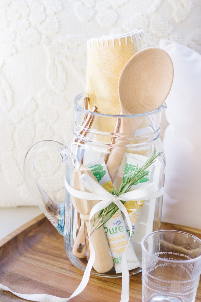 Close up of a unique Summer hostess gift comprised of a clear pitcher, lemonade packets, wooden mixing spoon, lemon juicer, white silicone ice cube tray, and yellow tea towel set on an acacia serving tray