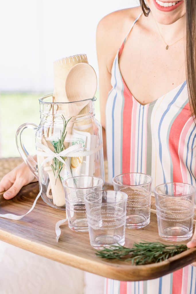 A woman in a striped dress holding unique Summer hostess gift comprised of a clear pitcher, lemonade packets, wooden mixing spoon, lemon juicer, white silicone ice cube tray, yellow tea towel and emboseed clear tumblers