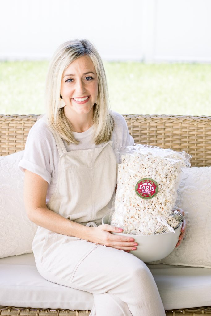 A woman wearing a cream jumper holding a cream stoneware bowl filled with a bag of white popcorn and everything bagel seasoning
