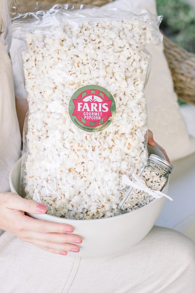 A close up of woman's hands holding a cream stoneware bowl filled with a bag of white popcorn and everything bagel seasoning