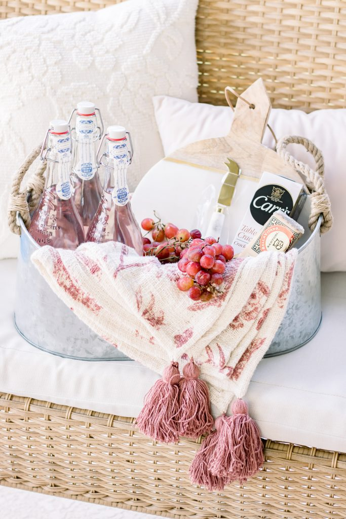 A unique Summer hostess gift idea comprised of a galvanized tub, decorative throw blanket, sparkling frech soda, marble cutting board, fresh grapes, specialty cheese and water crackers