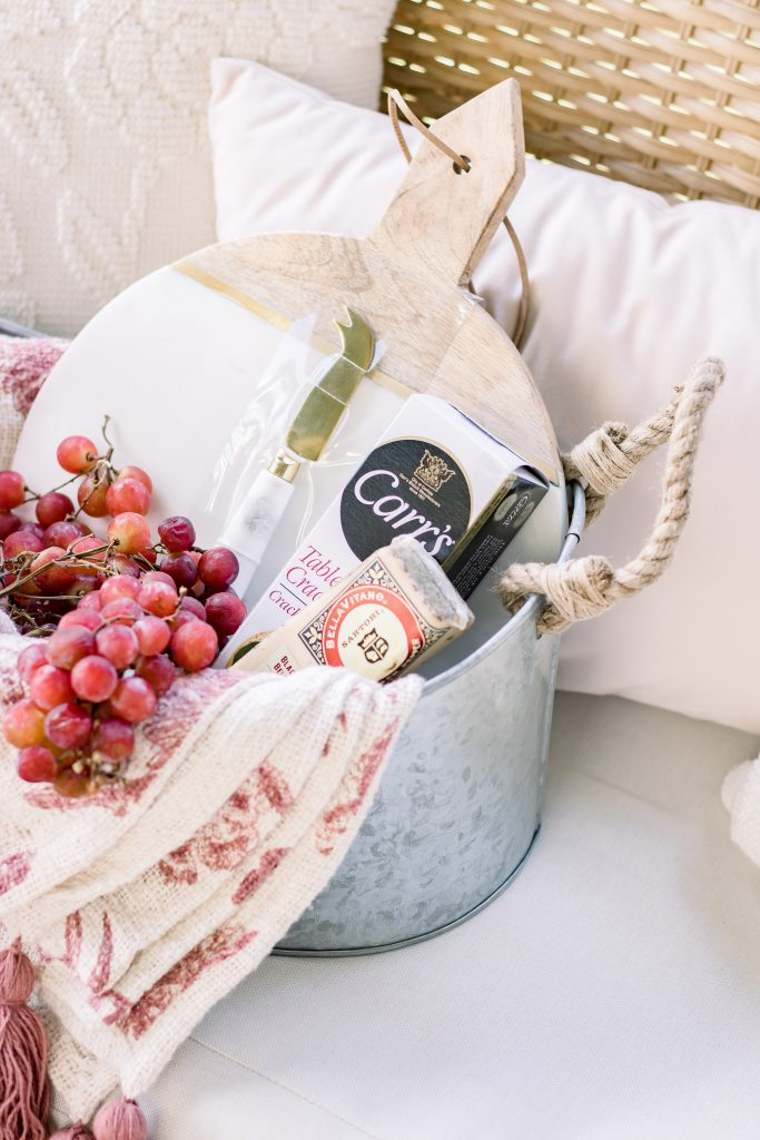 A closeup of marble cutting board in a galvanized bucket with specialty cheese, water crackers and fresh grapes for a unique summer hostess gift