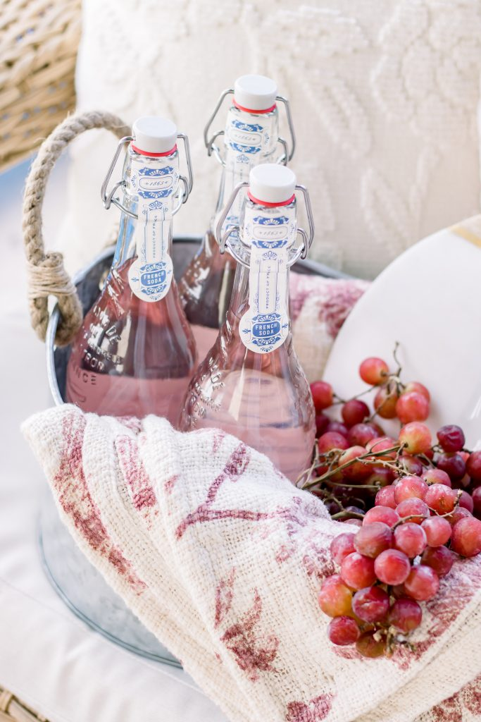 A close up of sparkling French soda in a galvanized bucket filled with a decorative throw blanket, fresh grapes and a marble cutting board for a unique Summer hostess gift