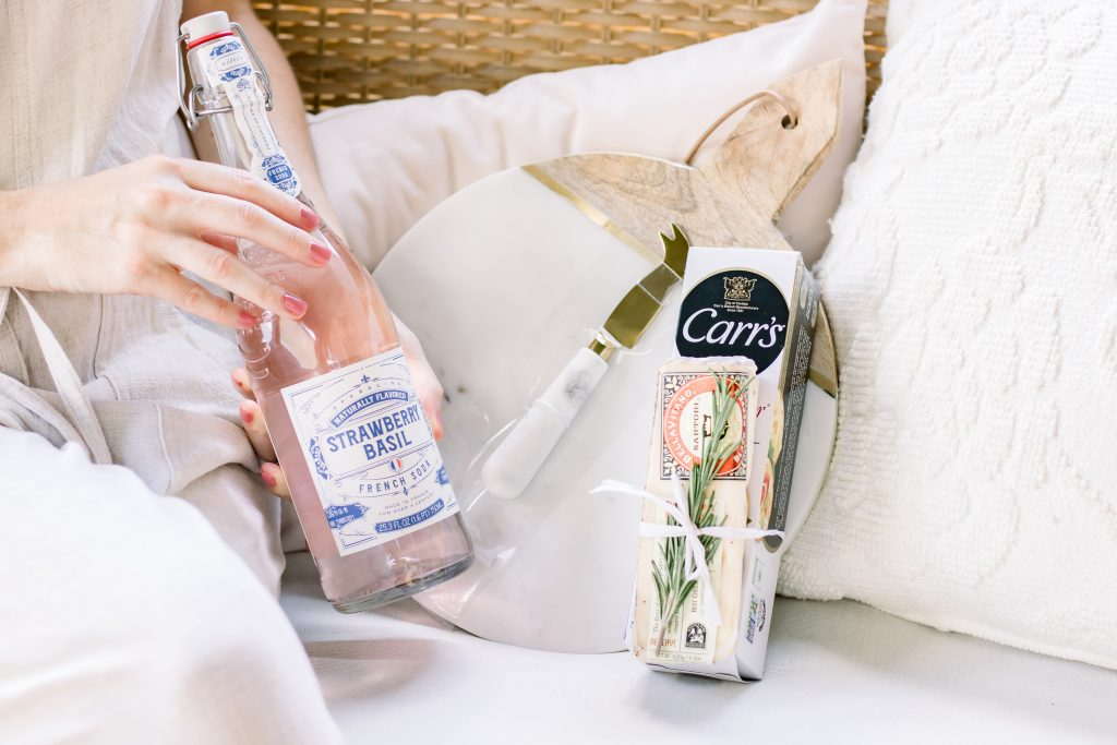 A close up of a woman's hands holding sparkling French soda next to a marble cutting board, specialty cheese and water crackers as a unique summer hostess gift idea