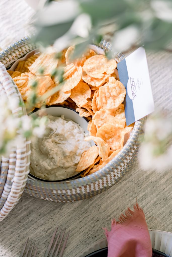Barbecue chips and carmelized onion dip in a grey and white seagrass lidded basket for a Labor Day Tablescape
