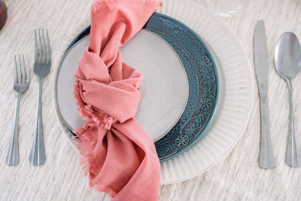 Closeup of Labor Day placesetting consisting of blue and white dinnerware and pink linen napkins