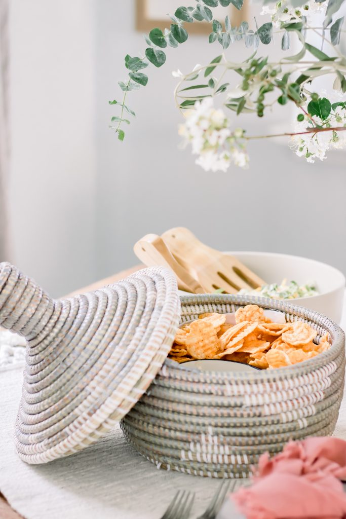 Grey and white seagrass lidded basket filled with chips and dip