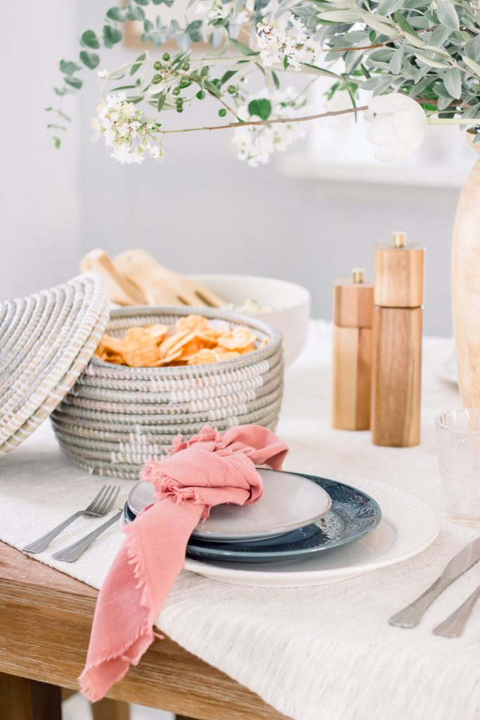 Sophisticated Labor Day tablescape with blue and white dinnerware and pink linen napkins