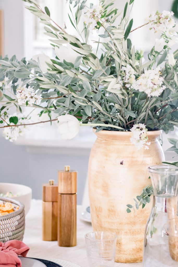 Greenery and white floral centerpieces in tall wood vase set on Labor Day tablescape