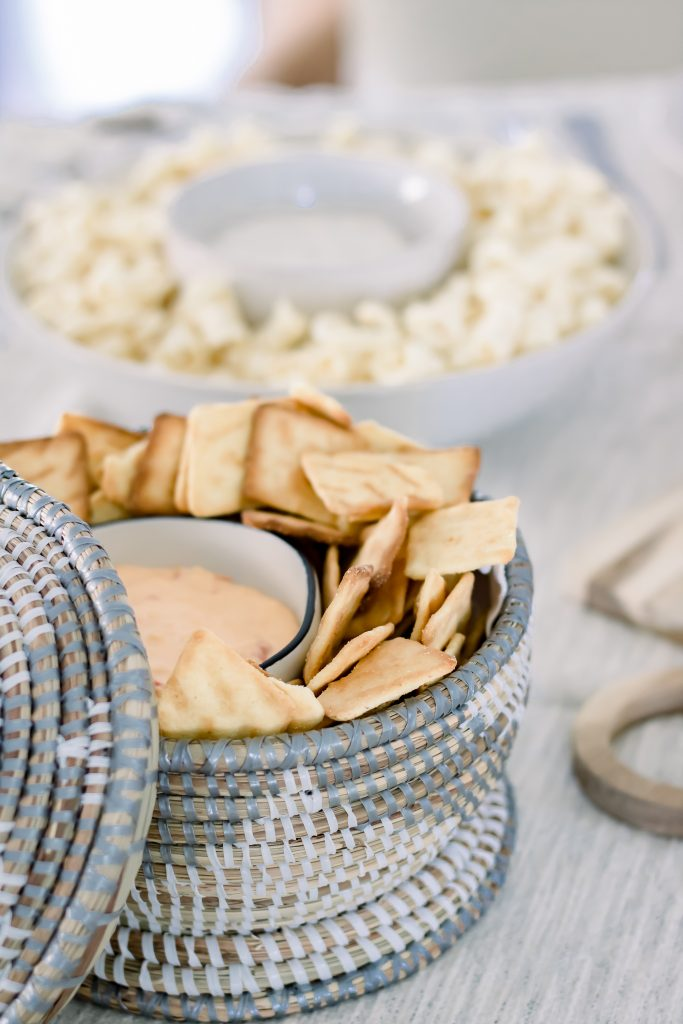 Grey and white seagrass lidded basket filled with Trader's Joe Cornbread Crackers and Pimento Cheese Dip