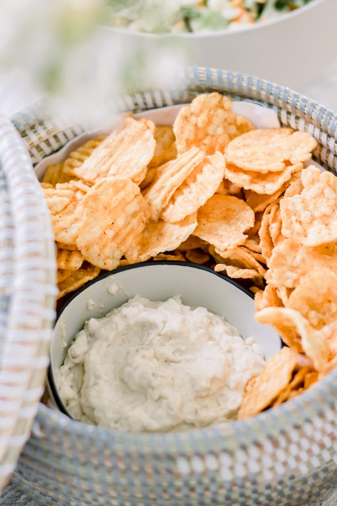 Grey and white seagrass lidded basket filled with Trader's Joe's Barbecue Popped Ridges and Caramelized Onion Dip