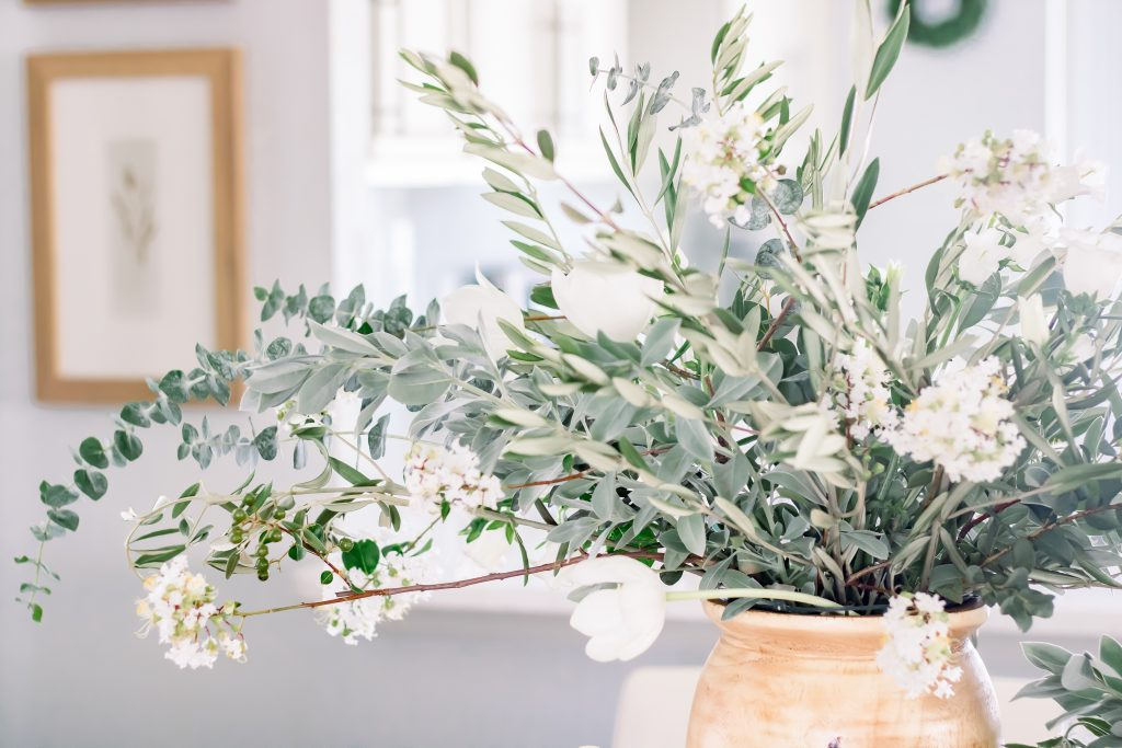Close up of greenery and white floral centerpiece