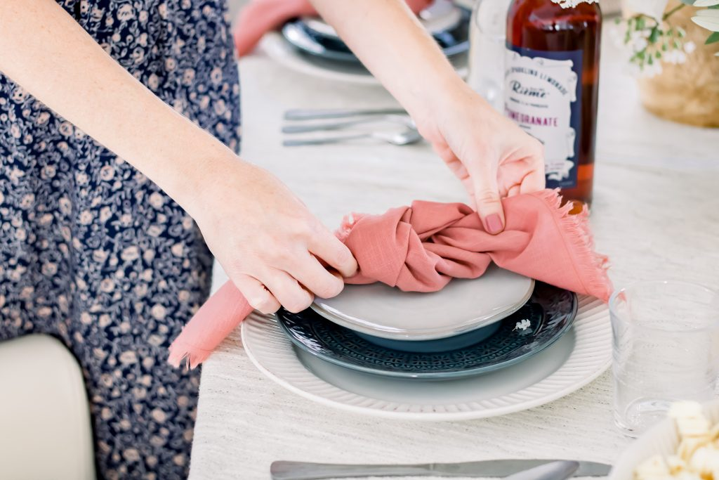 Closeup of two hands setting Labor Day place setting consisting of blue and white dinnerware and pink linen napkins